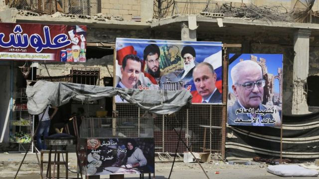 Portraits of (from L to R), Syrian President Bashar al-Assad, Lebanon's Hezbollah chief Hasan Nasrallah, Iran's supreme leader Ayatollah Ali Khamenei, Russian President Vladimir Putin and Khaled al-Assaad, the slain chief archaeologist of the ancient Syrian city of Palmyra, are seen in the eastern city of Deir Ezzor on September 20, 2017 as Syrian government forces continue to press forward with Russian air cover in the offensive against Islamic State group jihadists across the province. Two separate offensives are under way against the jihadists in the area -- one by the US-backed Syrian Democratic Forces, the other by Russian-backed government forces. The Syrian army now controls around 70 percent of the city and is battling to oust IS from the remainder, according to the Britain-based Observatory. / AFP PHOTO / LOUAI BESHARA (Photo credit should read LOUAI BESHARA/AFP/Getty Images)