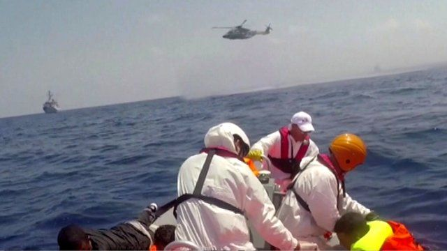 Rescuers searching for hundreds of migrants in the Mediterranean help a man out of the water