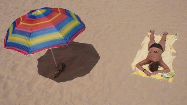 Женщина на пляже и тень от зонтика