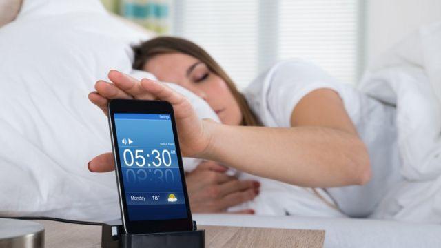 Mujer acostada con el celular en la mesa de noche