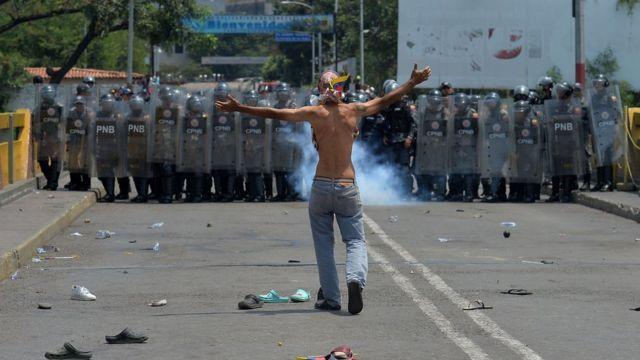 A demonstrator gestures in front of Venezuelan national policemen standing guard at the Simon Bolivar international bridge, in Cucuta