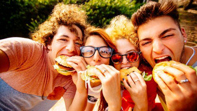 Un grupo de jóvenes comiendo hamburguesas.