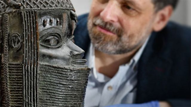 Neil Curtis, Head of Museums and Special Collections, dey wit a Bénin Bronze wey dey rep di Oba of Benin for di University of Aberdeen in Scotland