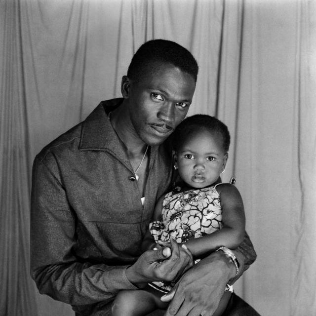 """Un homme et une petite fille posent dans le studio """"Studio Da Silva""""."""