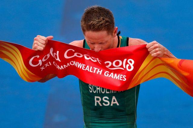 جنوبی افریقہ کے ہینری شومین مردوں کے ٹرائیتھلون فائنل مقابلے میں کامیابی کے بعد اختتامی بینر کو چومتے ہوئے۔