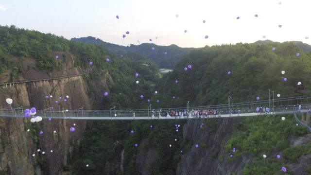 Couples and well wishes release balloons above Shiniuzhai glass bridge, 21 July 2016