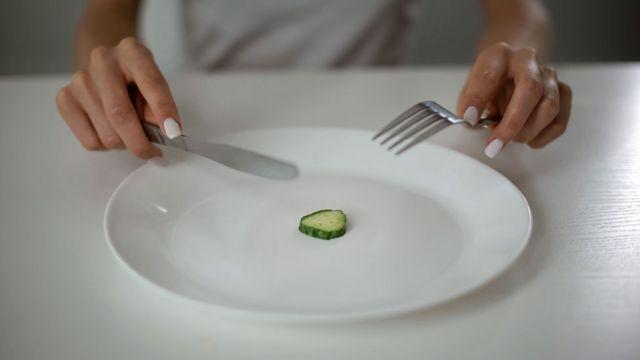 Una mujer comiendo un pedazo de pepino