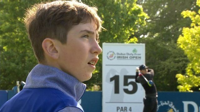 Tom McKibbin watches Rory McIlroy playing a shot