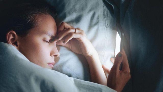 شابة تمسك هاتفها المحمول وهي نائمة في فراشها