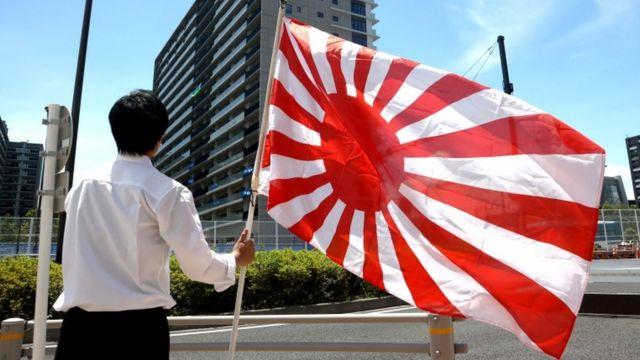Membro do grupo de extrema direita japonesa segura uma bandeira do Sol Nascente em frente ao prédio que hospeda a equipe olímpica sul-coreana na Vila Olímpica de Tóquio, no Japão, em 16 de julho de 2021