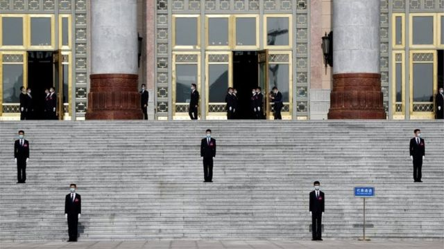 """Security personnel wearing face masks following the coronavirus disease (COVID-19) outbreak stand guard outside the Great Hall of the People before the opening session of the National People""""s Congress (NPC) in Beijing, China May 22, 2020."""