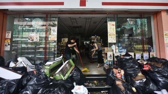 澳門一家被淹水的便利店內店員忙於清理(24/8/2017)