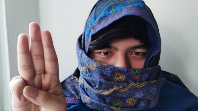 Burmese with purple sarong wrapped round his head doing a three finger salute.