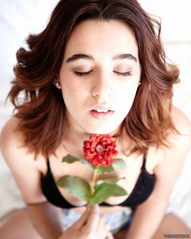 Imagen genérica de una mujer con cara de placer y una flor