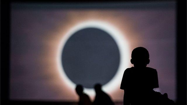 Bir uşaq tam Günəş tutulmasına ekranda baxır
