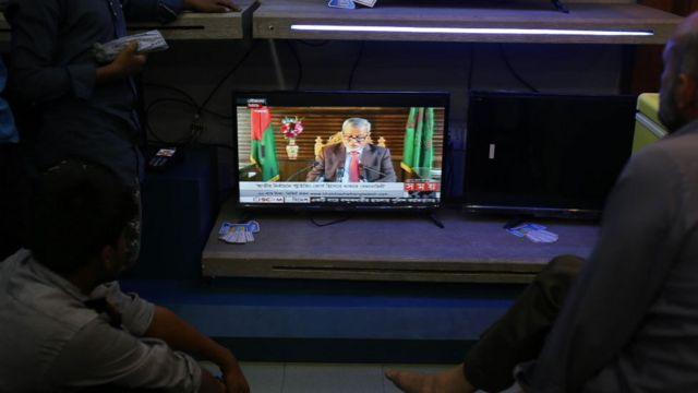 প্রধান নির্বাচন কমিশনার কেএম নুরুল হুদার টেলিভিশন বিবৃতি শুনছেন সাধারণ মানুষ।