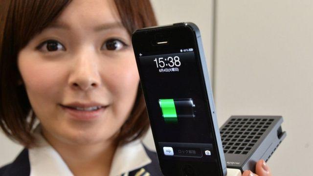 મોબાઈલ ફોન ચાર્જ કરી રહેલા મોબાઈલ ફોન ધારકની પ્રતિકાત્મક તસ્વીર