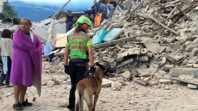 A man wrapped in blanket looks on as a rescuer with a dog stand in front a collapsed house