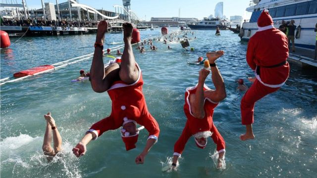 """Participants in a Santa Claus costume jump into the water during the 110th edition of the """"Copa Nadal"""" (Christmas Cup)"""