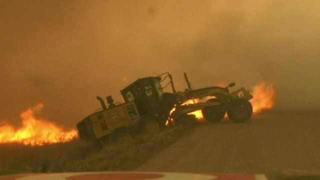 Road grader surrounded by fire