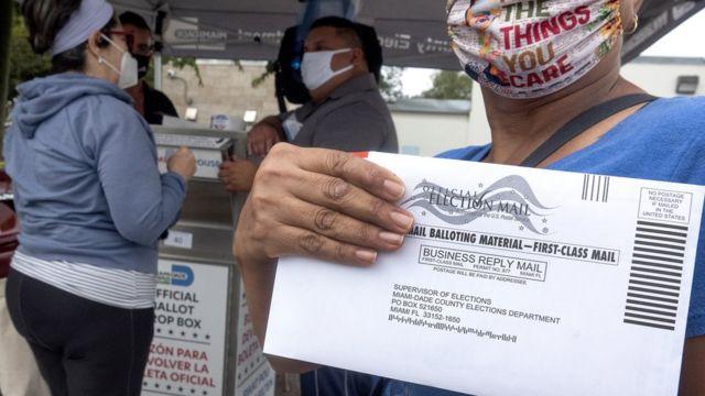 Una mujer con un sobre de votación en la mano