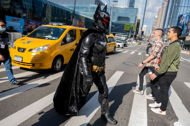 A cosplayer dressed as Batman wearing the Hellbat suit crosses the road during Day 1 of New York Comic Con at Javits Center on 7 October 2021 in New York City.