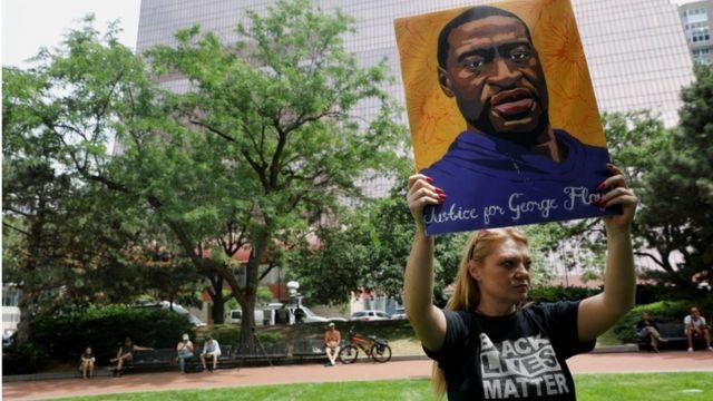 George Floyd'un pankartını tutan bir genç kadın