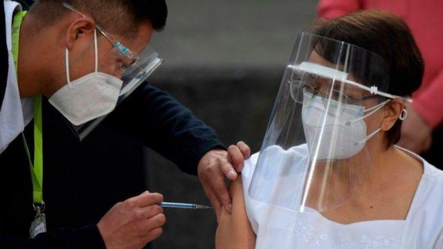 Uma enfermeira mexicana recebendo a vacina