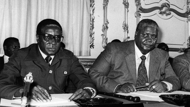 Robert Mugabe (kushotot) na Joshua Nkomo katika Lancaster House, Jijiji London.