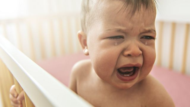 A baby in a cot crying