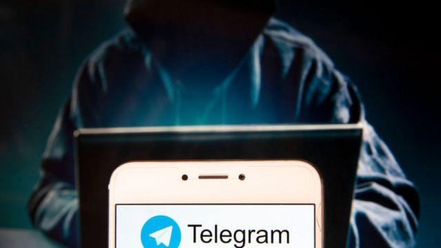 Ilustración de hacker y teléfono con el logo de Telegram.