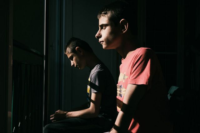 Two twin boys sit indoors next to a window