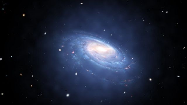 Artist's impression of a spiral galaxy with blue arms of dust and stars. A faint blue glow surrounds it.