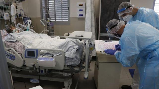 Paciente deitada e dois enfermeiros em sala de hospital