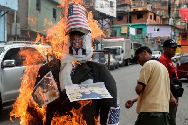 Un muñeco con fotos de Donald Trump y Mauricio Macri quemándose en el barrio 23 de enero de Caracas, Venezuela, el 16 de abril de 2017.