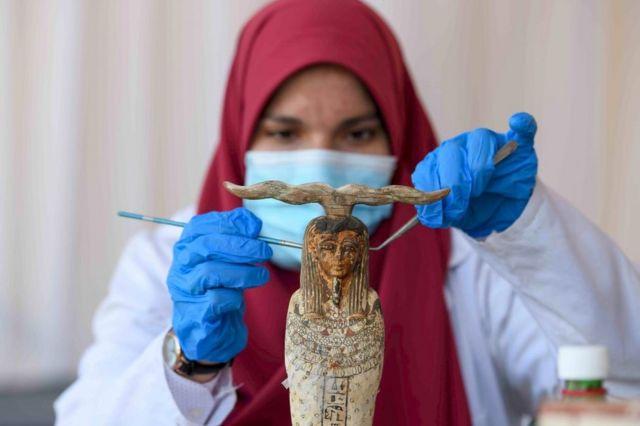 عالمة آثار تنظف تمثالاً فرعونياً صغيراً