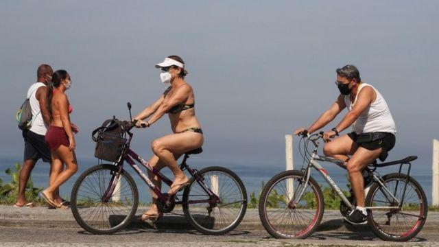 Pessoas usam máscara em calçadão na praia no Rio