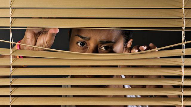 Mujer mirando por entre las persianas
