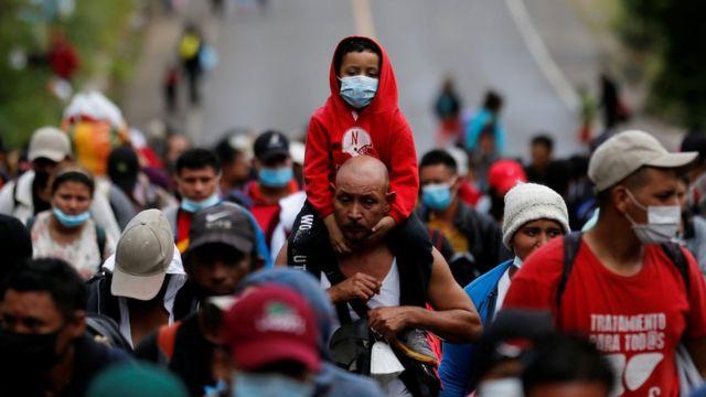 Un hombre lleva a un niño en sus hombros. Ambos integran la caravana de migrantes que partió de Honduras y pretende llegar a Estados Unidos.
