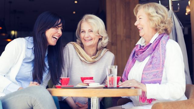 Two senior ladies and one young woman having coffee time in modern cafe