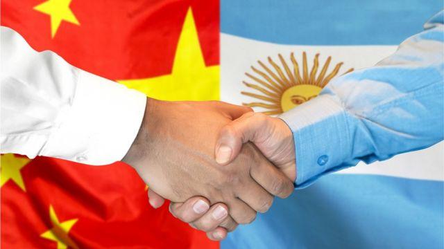 Apretón de manos frente a las banderas de China y Argentina