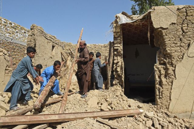 Residents remove debris of their damaged mud houses following an earthquake in the remote mountainous district of Harnai, Pakistan, on 7 October 2021