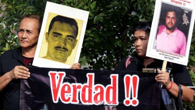 Manifestantes con carteles que muestran el rostro de sus familiares desaparecidos.