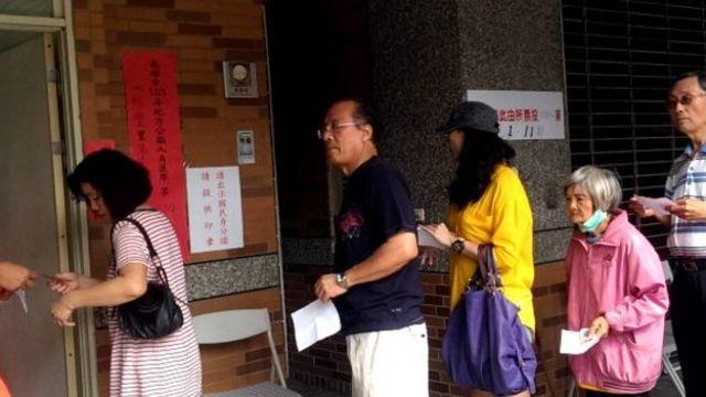 四年前的九合一地方选举,选民们在票站外排队。