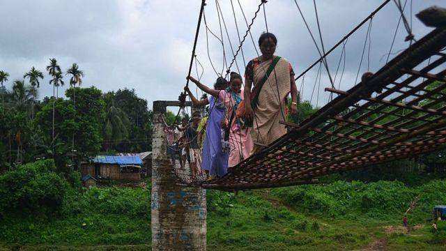 মেঘালয়ে শ্রী নদীর ওপর একটি সেতু পার হচ্ছেন কিছু গ্রামবাসী
