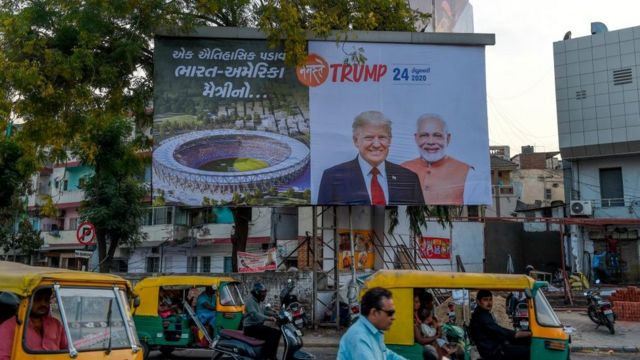 Vehicles pass below a billboard depicting US President Donald Trump and India's Prime Minister Narendra Modi in Ahmedabad on February 18, 2020.