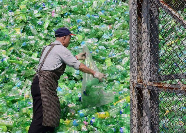 Un voluntario separa las botellas de plástico en una planta de reciclaje en Taipéi, Taiwán.