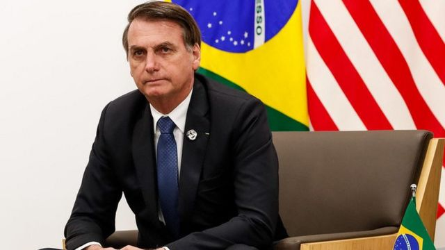 Bolsonaro is sitting in the room with the flags of the United States and Brazil behind them