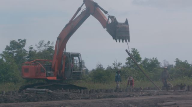BBC witnesses workers using heavy equipment digging out land near the canal and making the foundations of a building.