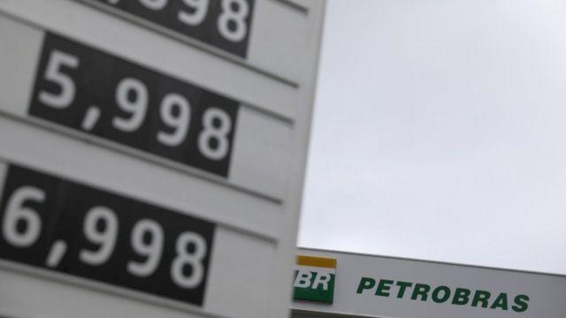 Placa com tabela de preços de combustíveis; ao fundo, outra placa traz nome em extenso da Petrobras